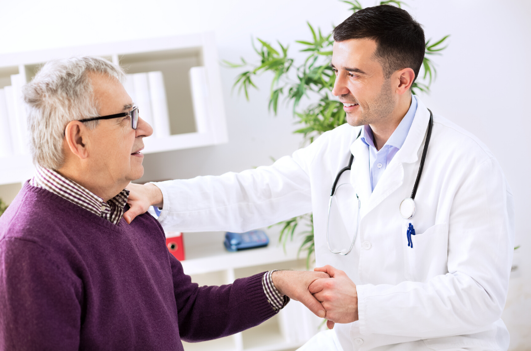 male doctor holding older male patient's hand